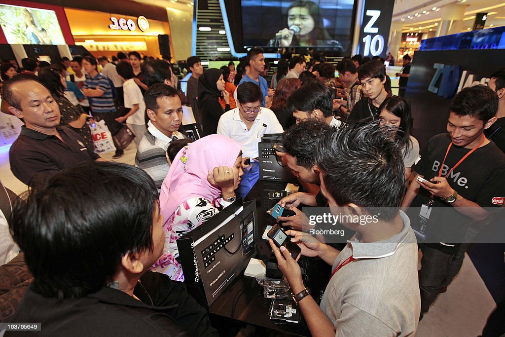 Sales assistants assist customers as they purchase the BlackBerry Z10 smartphone during the consumer launch of the device at the Central Park Mall in Jakarta, Indonesia, on Friday, March 15, 2013. BlackBerry, the Canadian smartphone maker that rolled out a new lineup in January, said one of its 'established partners' is buying 1 million BlackBerry 10 phones, the biggest order in the company's history. Photographer: Dimas Ardian/Bloomberg via Getty Images