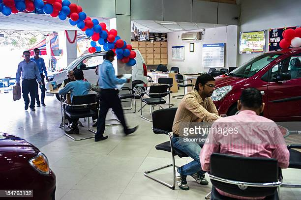 Sales assistants attend to customers inside a Maruti Suzuki India Ltd dealership in New Delhi India on Thursday Oct 25 2012 With only 13 percent of...