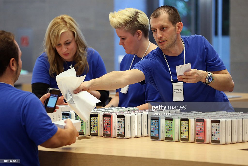 Sales assistants process purchases of the Apple iPhone 5C smartphones at the Berlin Apple Store on the first day of sales on September 20, 2013 in Berlin, Germany. The new iPhone 5S and 5C phones went on sale all over the world today and hundreds of customers waited outside the Berlin store in the rain to be among the first to buy the new phones starting at 8am.
