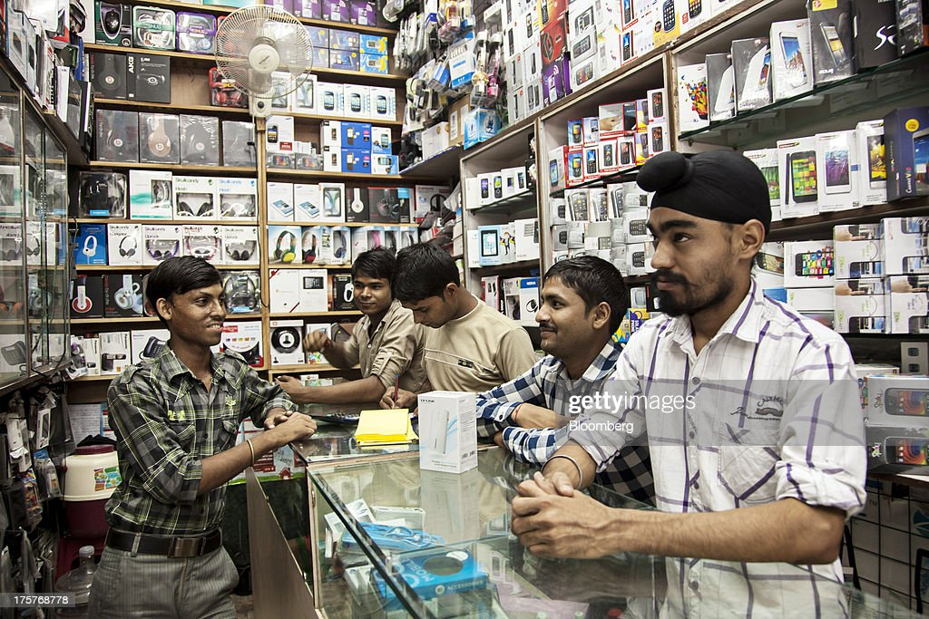 Sales assistants serve a customer at a store in Nehru Place IT Market, a hub for the sale of electronic goods and computer accessories, in downtown New Delhi, India, on Wednesday, Aug. 7, 2013. India's consumer price index (CPI) figures for July are scheduled to be released on August 12. Photographer: Graham Crouch/Bloomberg via Getty Images