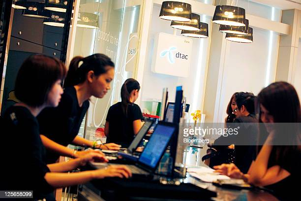 Sales assistants work at a Total Access Communication Pcl store at the company's headquarters in Bangkok Thailand on Monday Sept 19 2011 DTAC...