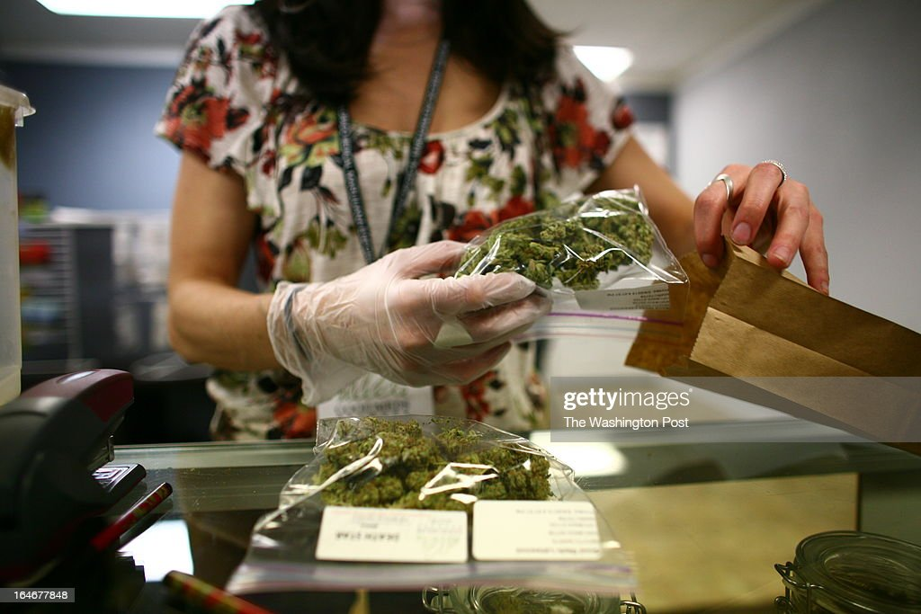 Sales associate, Crystal Guess packages up a patient's cannabis inside a Good Meds medical cannabis center in Lakewood, Colorado, U.S., on Monday, March 4, 2013. This is at a Good Meds medical cannabis center in Lakewood, and is one of the facilities that Kristi Kelly, Co-Founder of Good Meds Network, operates.
