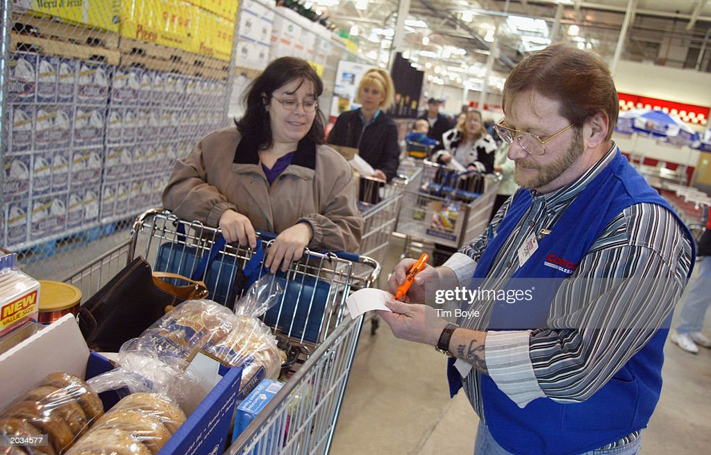Sales associate Don Ebert checks a shopper's purchase March 8 2002 at a Costco Wholesale store in Niles Illinois Warehouse retailer Costco Wholesale...