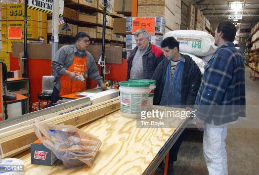 Sales associate Ernesto Martinez left assists contractors through a checkout line at a Home Depot store March 4 2002 in Mount Prospect IL Home Depot...