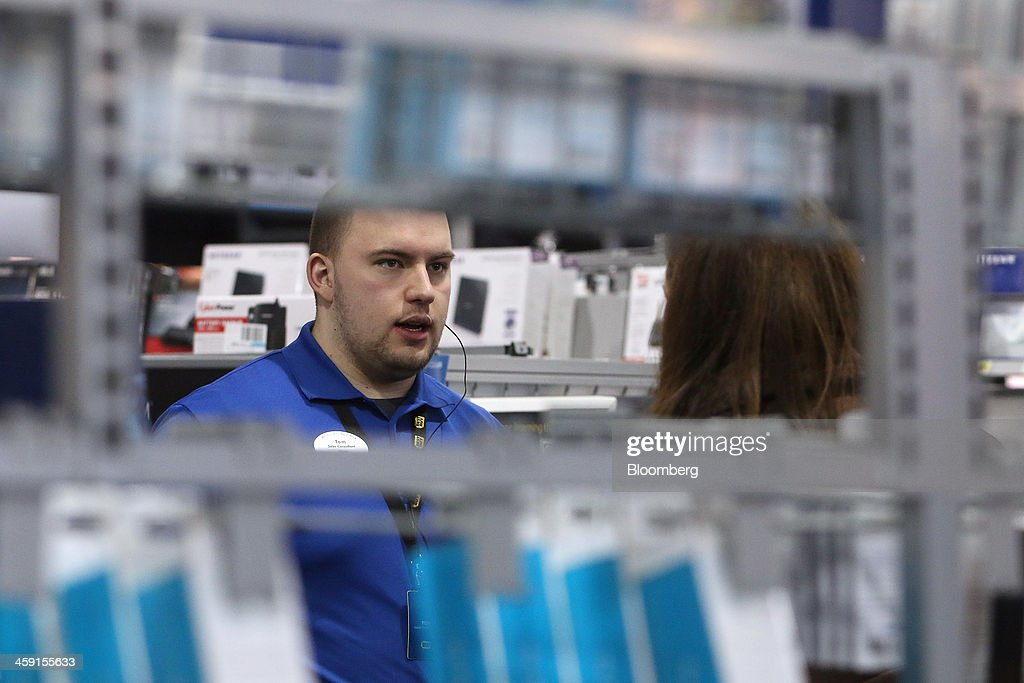A sales associate helps a customer at a Best Buy Co. store in Northbrook, Illinois, U.S., on Monday, Dec. 23, 2013. U.S. shoppers flocked to stores during the last weekend before Christmas as retailers piled on steeper, profit-eating discounts to maximize sales in their most important season of the year. Photographer: Tim Boyle/Bloomberg via Getty Images