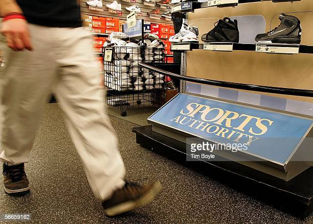 A sales associate walks past a Sports Authority sign near an athleticshoe display at a Sports Authority store January 24 2006 in Niles Illinois...