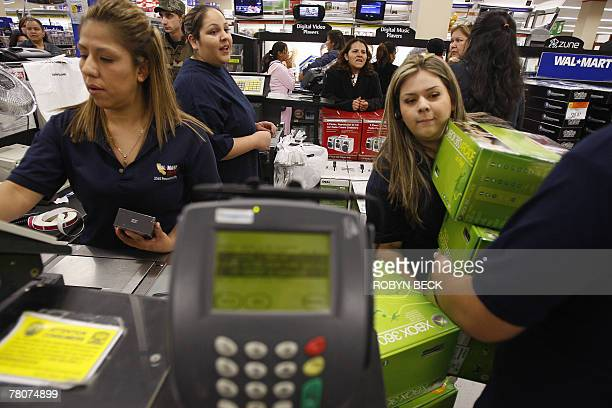 Sales associates bring Xbox game consoles to the counter for early morning shoppers at a WalMart store in Panorama City California 23 November 2007...