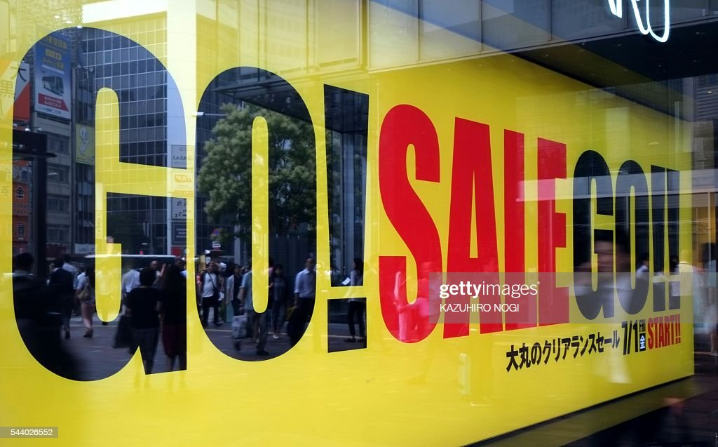 A sales campaign logo is displayed on a window of a department store in Tokyo on July 1, 2016. Japan was clobbered with a one-two punch July 1 morning as weak data and a lacklustre business confidence report underscored the slowdown dragging on the world's number three economy. / AFP / KAZUHIRO