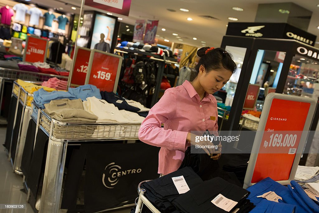 A sales clerk arranges clothing at the Discovery Shopping Mall in Kuta, Bali, Indonesia, on Tuesday, Oct. 8, 2013. Bank Indonesia said it will regulate currency hedging by individuals and companies, including state-owned firms, to help stabilize Asias most-volatile currency. Photographer: SeongJoon Cho/Bloomberg via Getty Images