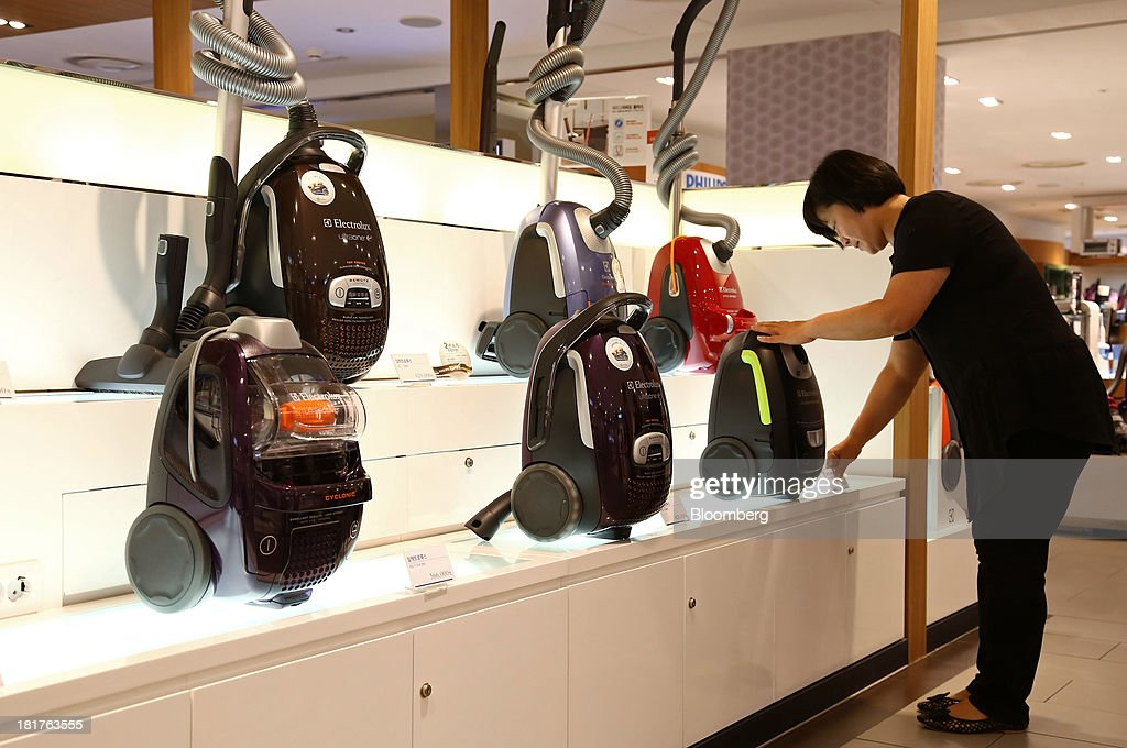 A sales clerk arranges Electrolux AB vacuum cleaners at a Shinsegae Co. department store in Seoul, South Korea, on Tuesday, Sept. 24, 2013. The South Korean economy faces headwinds, with record household debt and a sluggish housing market weighing on consumption. Photographer: SeongJoon Cho/Bloomberg via Getty Images