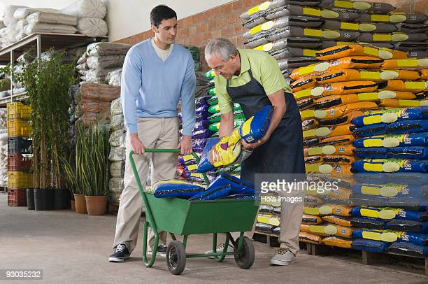 Sales clerk arranging fertilizer's bag in shopping cart