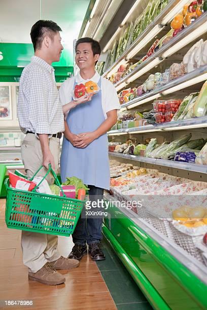Sales clerk assisting man in supermarket, Beijing
