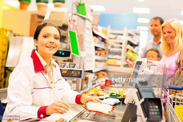 Employé de magasin à la caisse enregistreuse dans le supermarché
