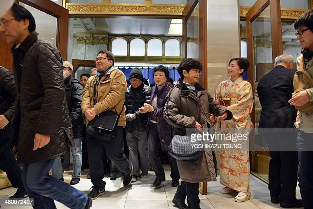 A sales clerk greets New Year shoppers as they rush into a department store to buy 'lucky bags' containing items worth three times as much as their...