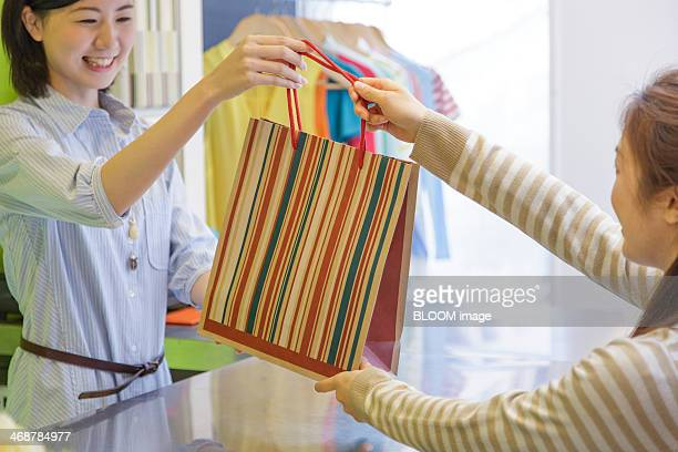 Sales clerk handing shopping bag to costumer