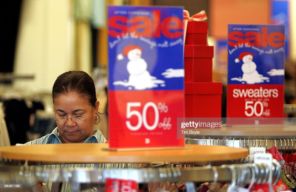 Sales clerk Marva Glass arranges sale items near 'After-Christmas Sale' signage in a Dress Barn store December 27, 2005 in Mount Prospect, Illinois. Retailers are marking down prices as consumers are looking for post-Christmas deals.