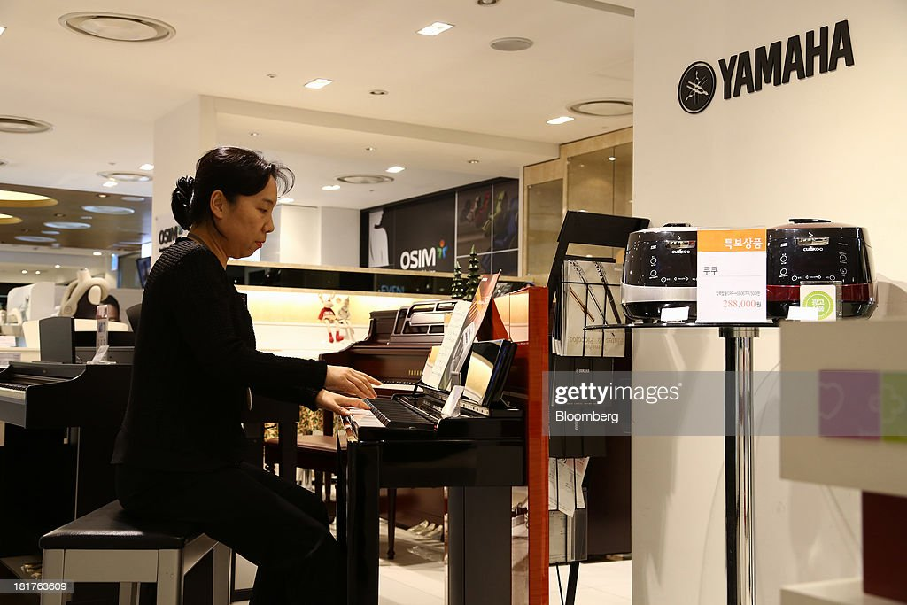 A sales clerk plays a Yamaha Corp. piano at a Shinsegae Co. department store in Seoul, South Korea, on Tuesday, Sept. 24, 2013. The South Korean economy faces headwinds, with record household debt and a sluggish housing market weighing on consumption. Photographer: SeongJoon Cho/Bloomberg via Getty Images