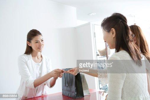 Sales clerk receiving credit card from costomer