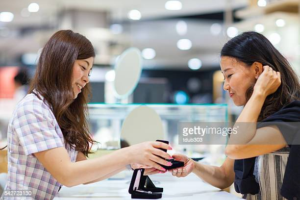 Sales clerk showing jewellery to a customer