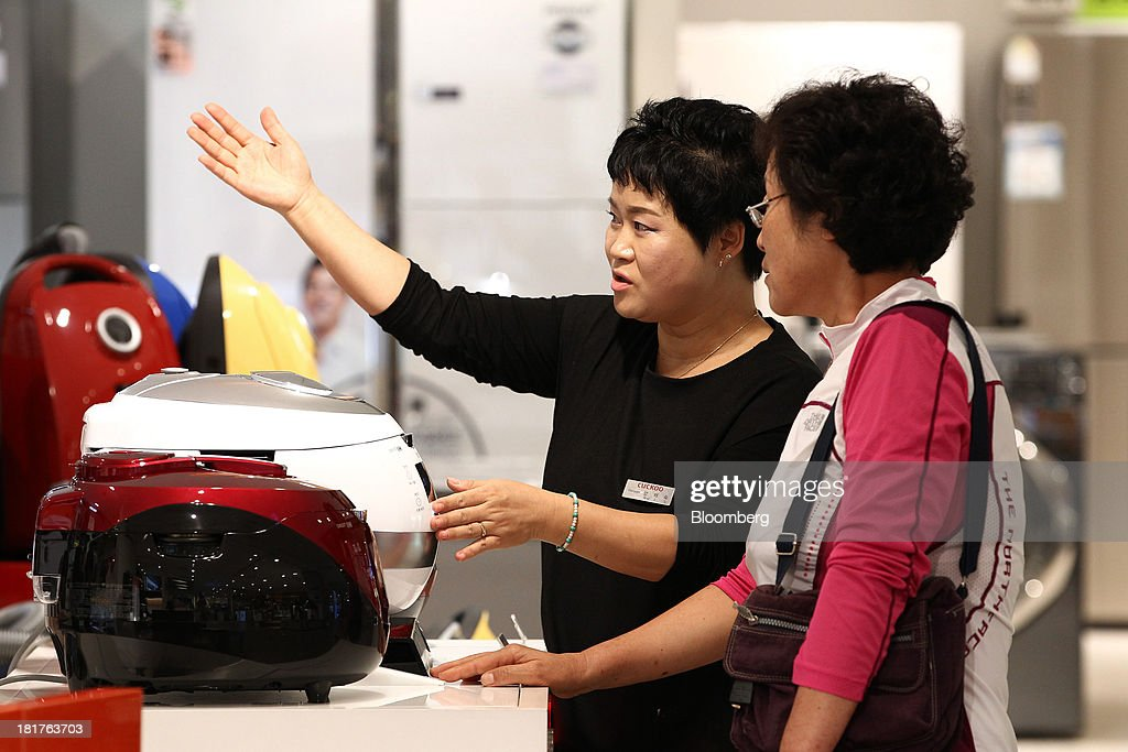 A sales clerk shows a customer Cuckoo Electronics Co. electric rice cookers in a Shinsegae Co. department store in Seoul, South Korea, on Tuesday, Sept. 24, 2013. The South Korean economy faces headwinds, with record household debt and a sluggish housing market weighing on consumption. Photographer: SeongJoon Cho/Bloomberg via Getty Images