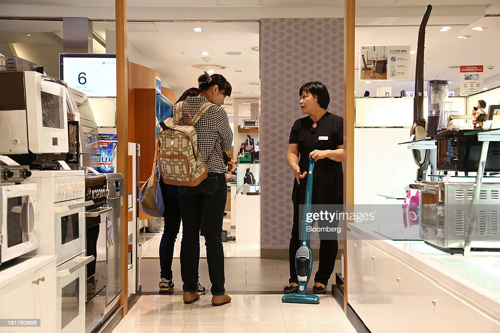 A sales clerk shows an Electrolux AB vacuum cleaner to customers at a Shinsegae Co. department store in Seoul, South Korea, on Tuesday, Sept. 24, 2013. The South Korean economy faces headwinds, with record household debt and a sluggish housing market weighing on consumption. Photographer: SeongJoon Cho/Bloomberg via Getty Images