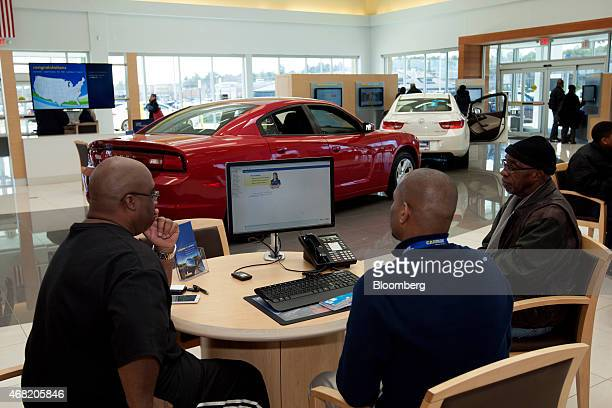 Sales consultant Andre Griffith center center show customers information on a computer at a CarMax Inc dealership in Brandywine Maryland US on Sunday...