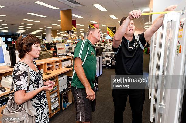 Sales consultant James Campbell right measures a refrigerator for customers Amanda and Mark Minenkoff at a Harvey Norman Holdings Ltd store in...