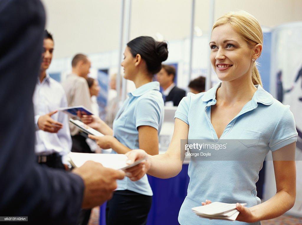sales executives distributing brochures to business executives at an exhibition