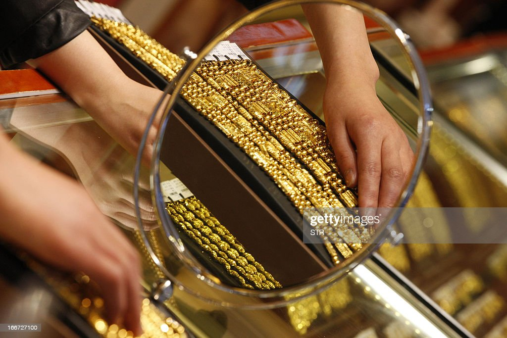 A sales girl arranges gold necklaces in a shop in Huaibei, central China's Anhui province on April 16, 2013. Gold prices recovered slightly on April 16 after suffering their heaviest slump in 30 years triggered by weak Chinese growth data and reports Cyprus was planning to sell part of its reserves. CHINA OUT AFP PHOTO