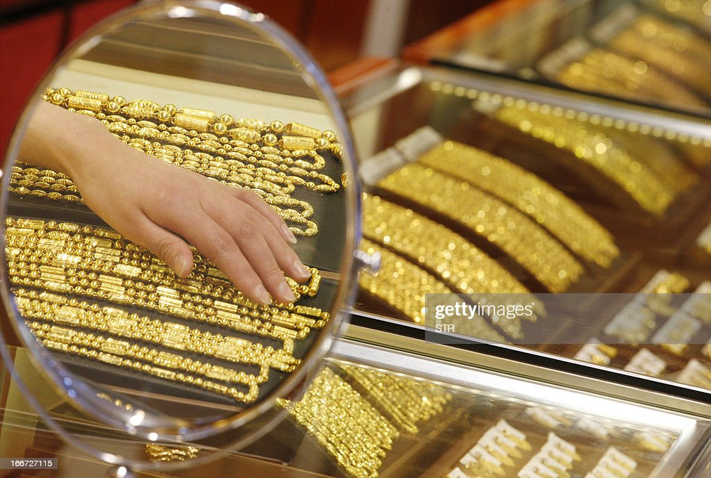 A sales girl arranges gold necklaces in a shop in Huaibei, central China's Anhui province on April 16, 2013. Gold prices recovered slightly on April 16 after suffering their heaviest slump in 30 years triggered by weak Chinese growth data and reports Cyprus was planning to sell part of its reserves. CHINA