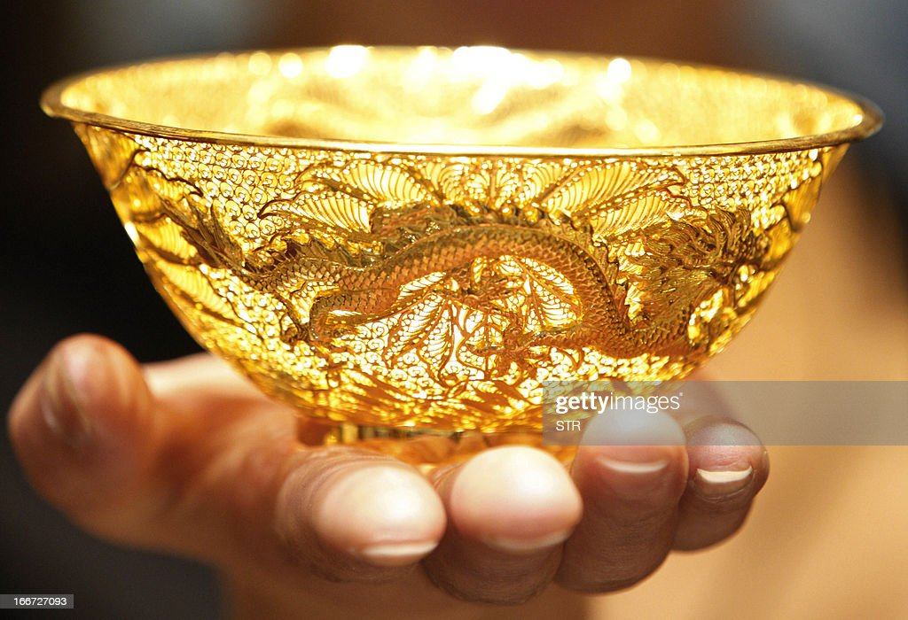 A sales girl displays a gold bowl in a shop in Huaibei, central China's Anhui province on April 16, 2013. Gold prices recovered slightly on April 16 after suffering their heaviest slump in 30 years triggered by weak Chinese growth data and reports Cyprus was planning to sell part of its reserves. CHINA
