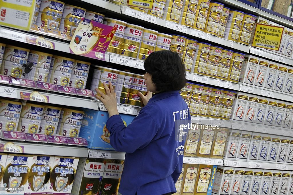 A sales girl puts baby milk powder on shelves in a supermarket in Nanjing, east China's Jiangsu province on March 29, 2013. The Chinese partner of Hero Group, a major Swiss baby formula manufacturer, has been accused of deliberately mislabelling milk powder and a senior employee has been detained, officials said on March 26, 2013. CHINA OUT AFP PHOTO