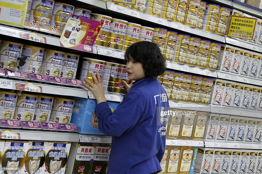 A sales girl puts baby milk powder on shelves in a supermarket in Nanjing, east China's Jiangsu province on March 29, 2013. The Chinese partner of Hero Group, a major Swiss baby formula manufacturer, has been accused of deliberately mislabelling milk powder and a senior employee has been detained, officials said on March 26, 2013. CHINA