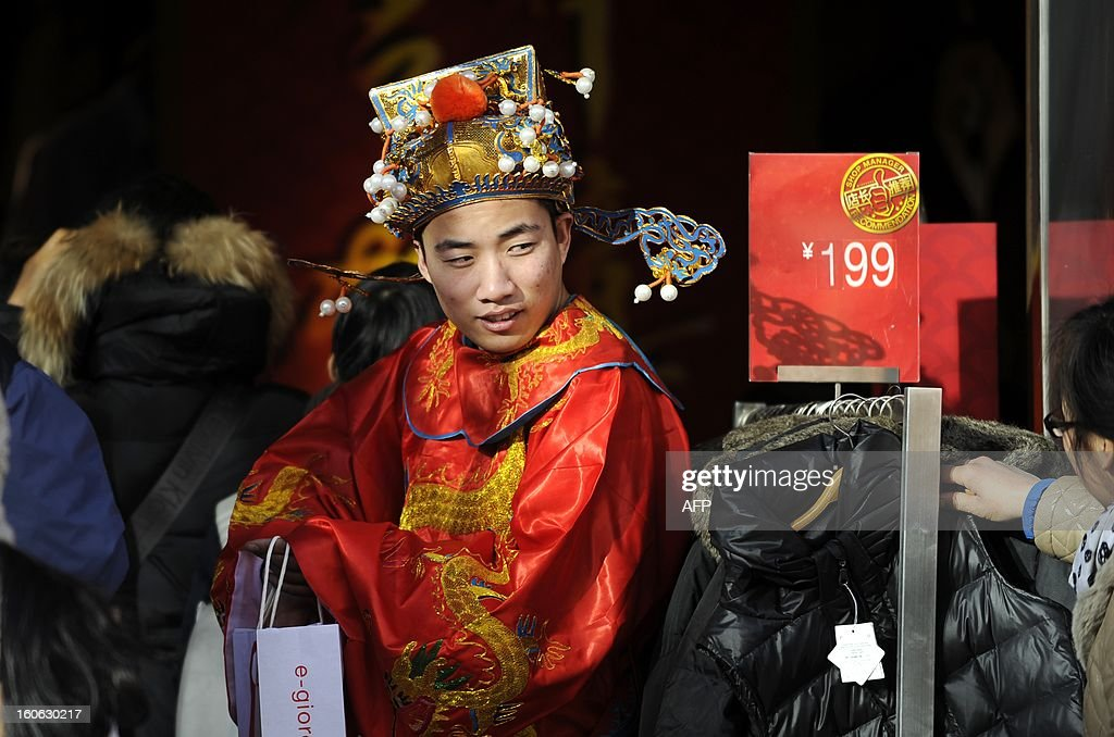 A sales man dressed as the god of wealth waits for customers at a sales promotion for the upcoming Lunar New Year at the entrance of a clothing store in Beijing on February 4, 2013. The Chinese New Year known locally as the Spring Festival, causes the world's largest annual migration of people with millions of travellers boarding public transport to journey across the vast country for the Lunar New Year celebrations. The government estimates the number of passenger trips on trains, planes, boats and buses will reach 3.2 billion during the holiday, up 9.1 percent from last year.