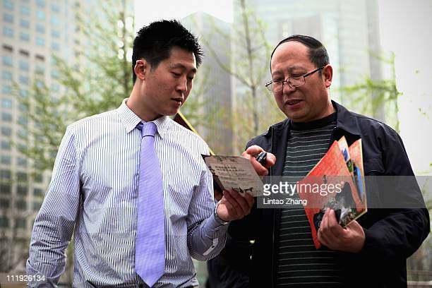 A sales person introduces properties to a potential buyer at the 2011 Beijing Spring Real Estate Trade Fair on April 9 2011 in Beijing China Property...