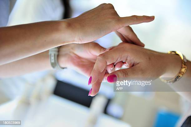A sales person tries a new product on a customers hand during the 5th Korea Beauty and Cosmetic Expo in Goyang north of Seoul on September 14 2013...