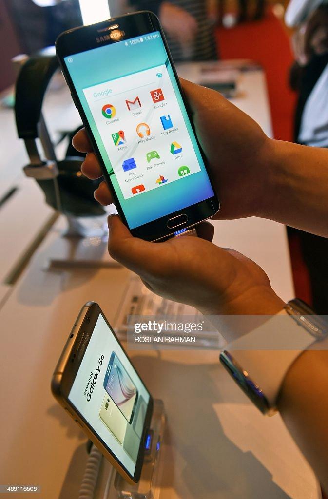 A sales representative displays the new Samsung Galaxy S6 ...