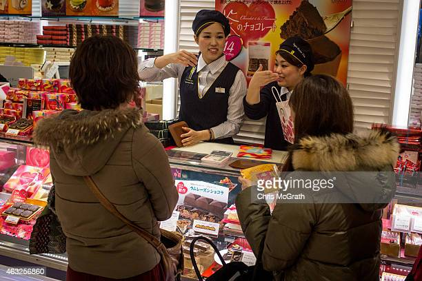 Sales staff discuss specialty chocolates with shoppers at a chocolate store on February 12 2015 in Tokyo Japan In Japan Valentine's day is celebrated...