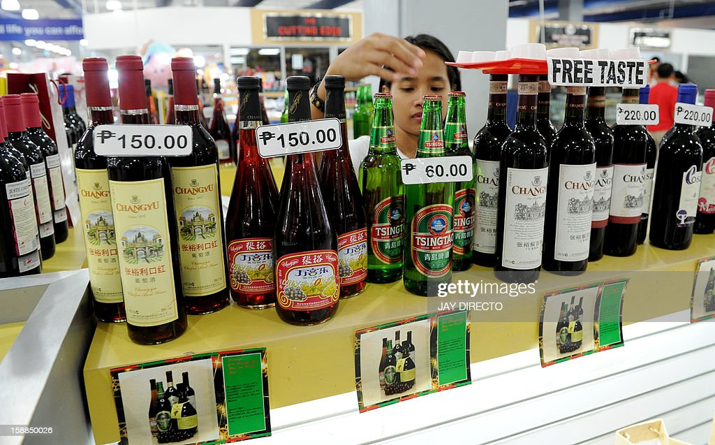 A sales staff member arranges alcoholic beverages at a mall in Manila on January 1, 2013. A 'sin tax' on cigarettes and alcohol dampened the New Year party spirit when it was introduced in the Philippines on January 1, as part of a government bid to boost finances.