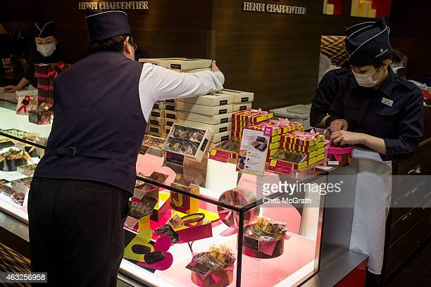 Sales staff pack valentines day gift boxes at a chocolate store in a department store on February 12 2015 in Tokyo Japan In Japan Valentine's day is...