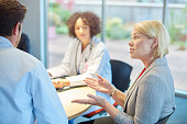 a mixed group of healthcare professional and business people meet around a conference table .