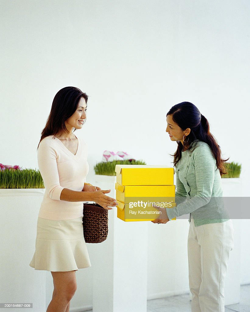 Sales woman handing over shoe boxes to female customer