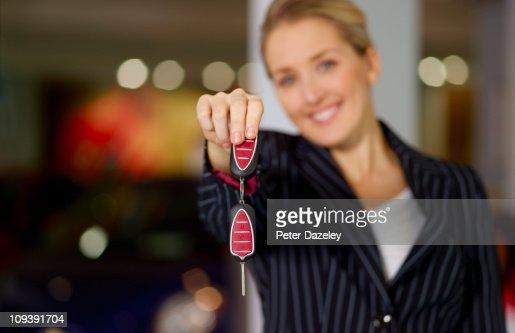 Sales woman holding car key landscape : Stock Photo