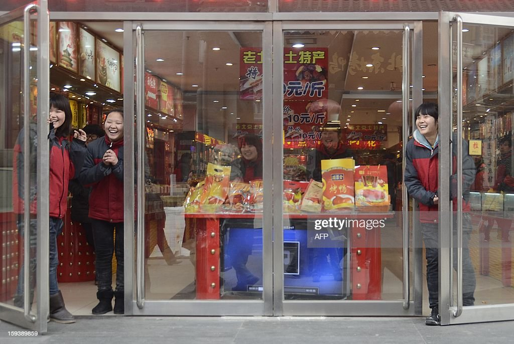 Sales women laugh as they wait for customers at the entrance of a shop in Beijing on January 13, 2013. China's economy is poised finally to end a long downward trend in 2013, economists polled by AFP say, as the new communist leadership vows to retool the nation's investment-led development model and promote a 'happy life' for all.