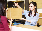 young female asian salesclerk handing a paper bag of merchandise to a customer at the check-out counter
