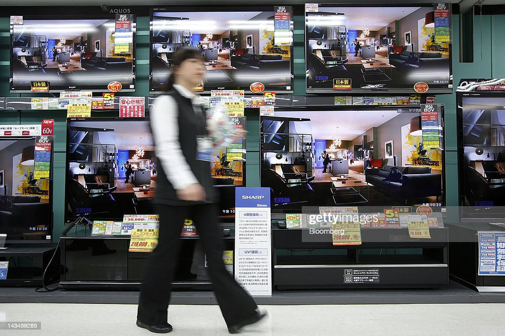 A salesclerk walks past Sharp Corp. Aquos liquid crystal display (LCD) televisions at the Labi Ofuna electronics store, operated by Yamada Denki Co., in Yokohama City, Kanagawa Prefecture, Japan, on Friday, April 27, 2012. Sharp Corp., Japan's biggest maker of LCD panels, forecast a net loss wider than analyst estimates as falling TV prices prompted the company to turn to Foxconn Technology Group for investment. Photographer: Kiyoshi Ota/Bloomberg via Getty Images