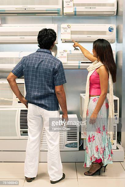 Salesgirl showing air conditioner to man in supermarket