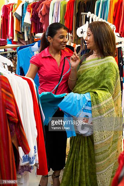 Salesgirl showing dress to customer in supermarket