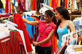 Salesgirl showing dress to woman in supermarket