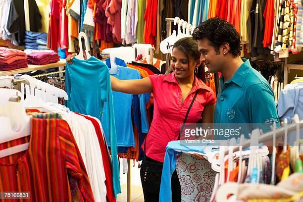 Salesgirl showing t-shirt to man in supermarket